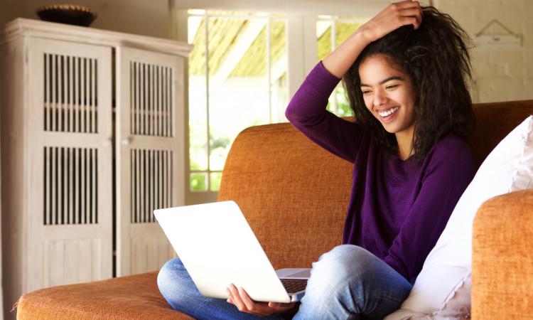 Bild von vergnügtem Mädchen am Sofa mit Laptop